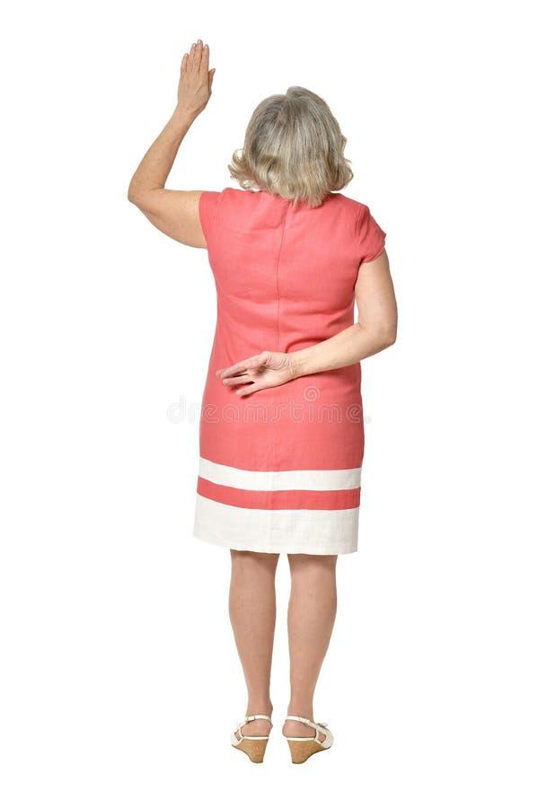 Mano d'ondeggiamento della donna senior su fondo bianco immagini stock libere da diritti