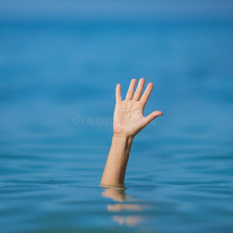 Mano de ahogar al hombre en el mar o el océano que pide ayuda fotos de archivo
