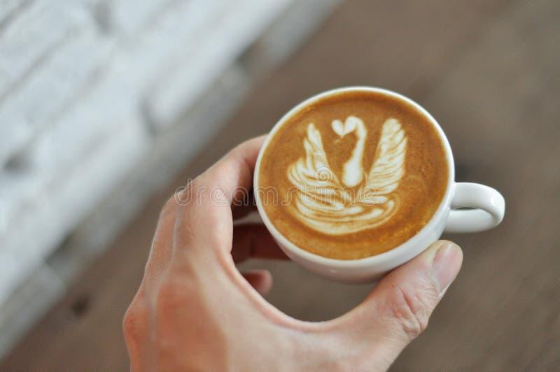 Mano de Barista que sostiene la taza de café con su arte del latte imagen de archivo