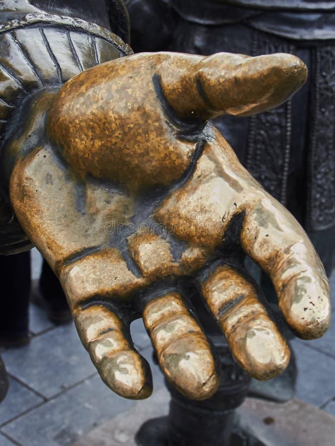 Mano de bronce de los resplandores de la amistad con los apretones de manos imagen de archivo