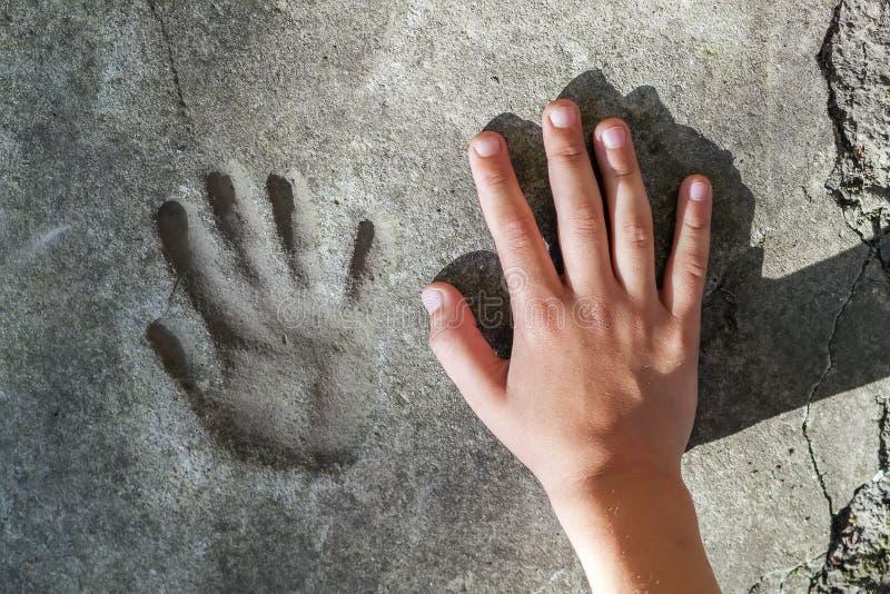 Mano de Childs y handprint memorable en hormigón fotografía de archivo