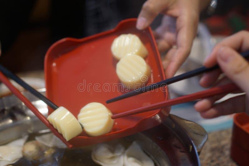 Mano de Diner's usando los palillos con la comida imagen de archivo