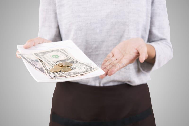 Mano de la camarera que lleva a cabo el cambio del dinero de la bandeja foto de archivo libre de regalías