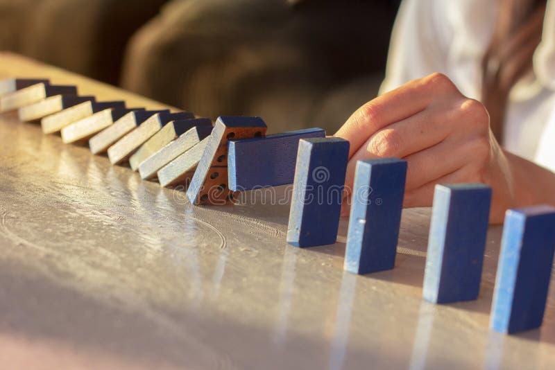 Mano de la empresaria que intenta parar el derribar de dominós en la tabla foto de archivo