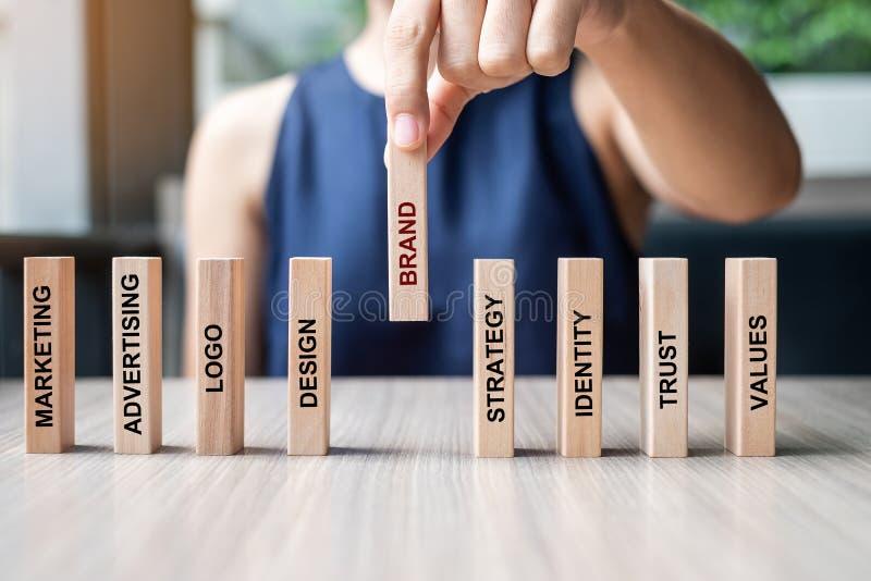 Mano de la empresaria que pone o que tira de domin?s de madera con el texto de la MARCA y m?rketing, publicidad, logotipo, dise?o foto de archivo libre de regalías