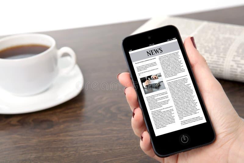 Mano de la empresaria que sostiene un teléfono con noticias de negocio contra el th imagen de archivo libre de regalías