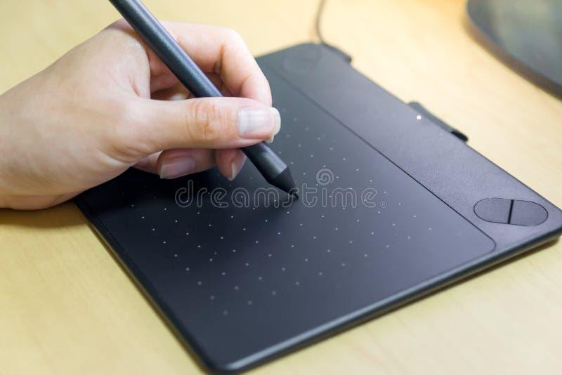 Mano de la escritura con la tableta gráfica foto de archivo libre de regalías