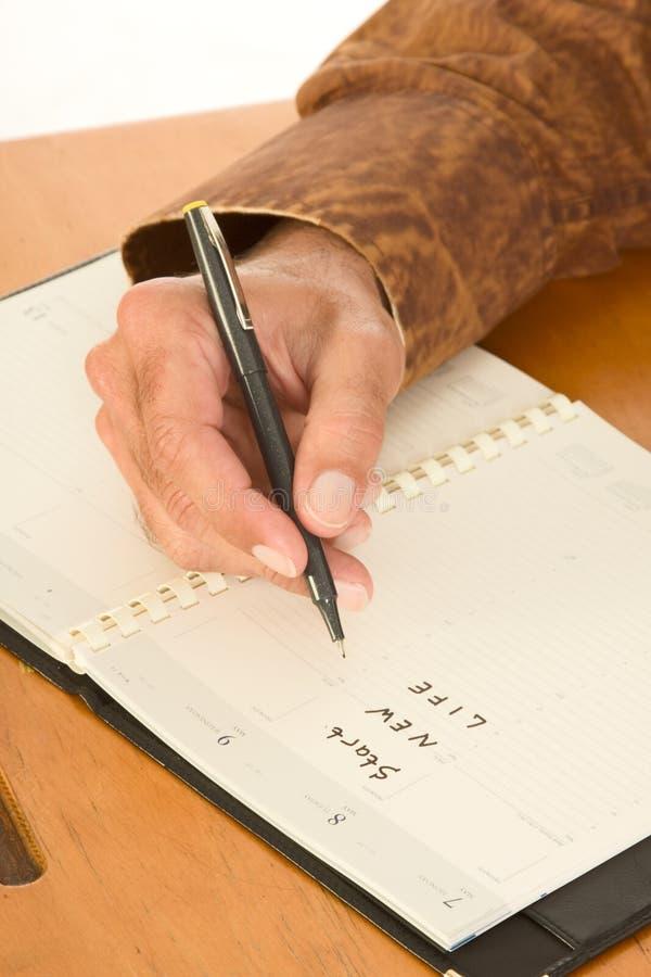 Mano De La Escritura Del Hombre En Planificador Del Día Sobre Nueva ...