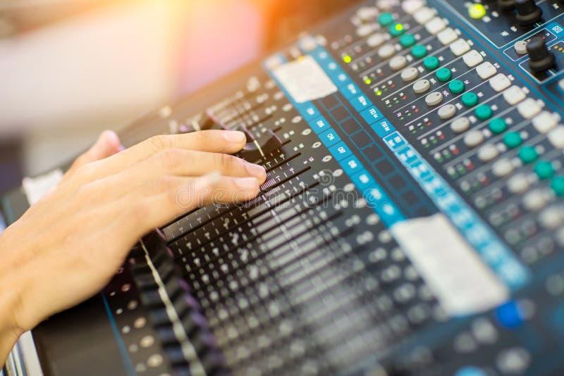 Mano de la foto de la falta de definición que ajusta el mezclador audio El ingeniero de sonido da el trabajo en mezclador de soni fotos de archivo