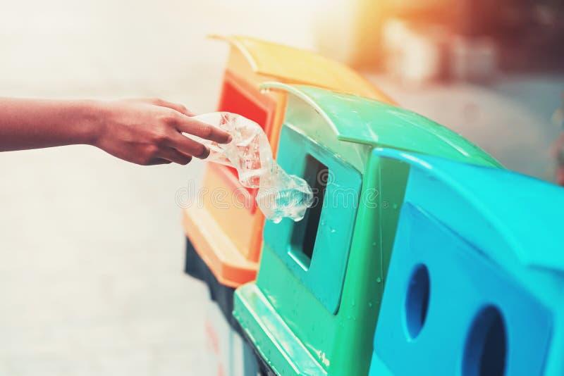 mano de la gente que sostiene el plástico de la botella de la basura que pone en la papelera de reciclaje para limpiar imagen de archivo