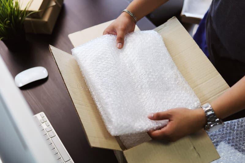 Mano de la hoja del plástico de burbujas o de la burbuja de la tenencia del hombre de negocios para envolver cerca de la caja del fotos de archivo libres de regalías