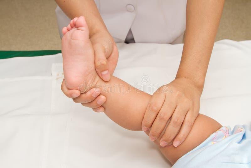 Mano de la madre que da masajes a la pierna de su bebé imagenes de archivo