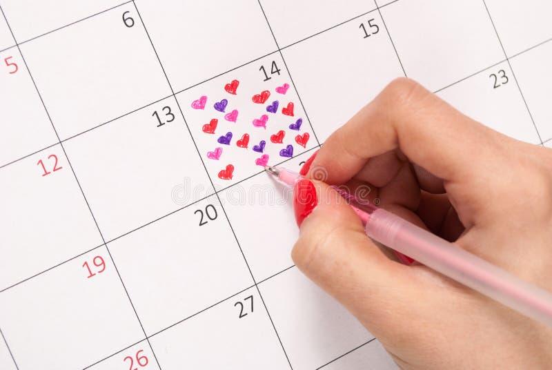 Mano de la muchacha con forma del corazón del dibujo de lápiz en el calendario para el día de tarjetas del día de San Valentín fotos de archivo