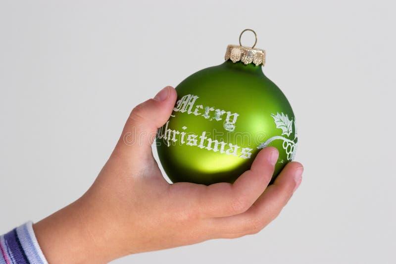 Mano de la muchacha con la bola de la Navidad foto de archivo libre de regalías
