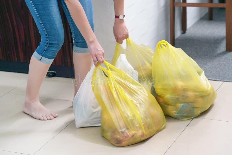 Mano de la muchacha con los bolsos de la comida en casa foto de archivo libre de regalías