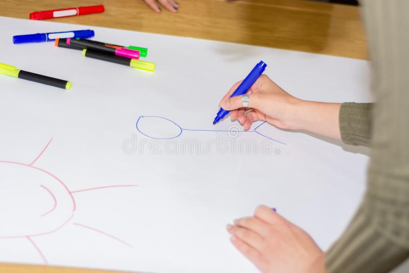 Mano de la muchacha con stickman sentido azul del dibujo de la pluma en el Libro Blanco grande en el escritorio en sala de clase imagenes de archivo