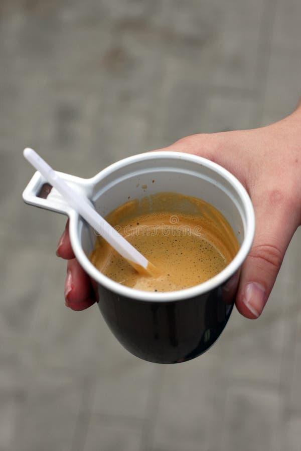 Mano de la muchacha con una taza de café foto de archivo