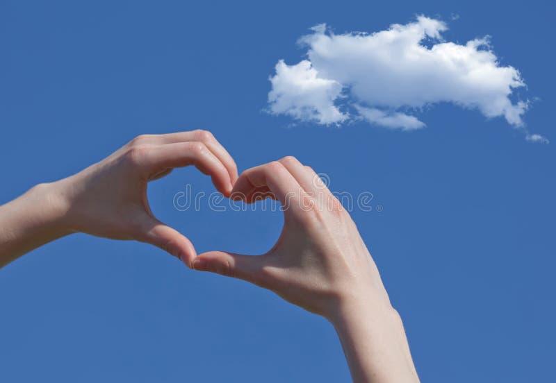 Mano de la muchacha en cielo azul del amor de la forma del corazón fotografía de archivo libre de regalías