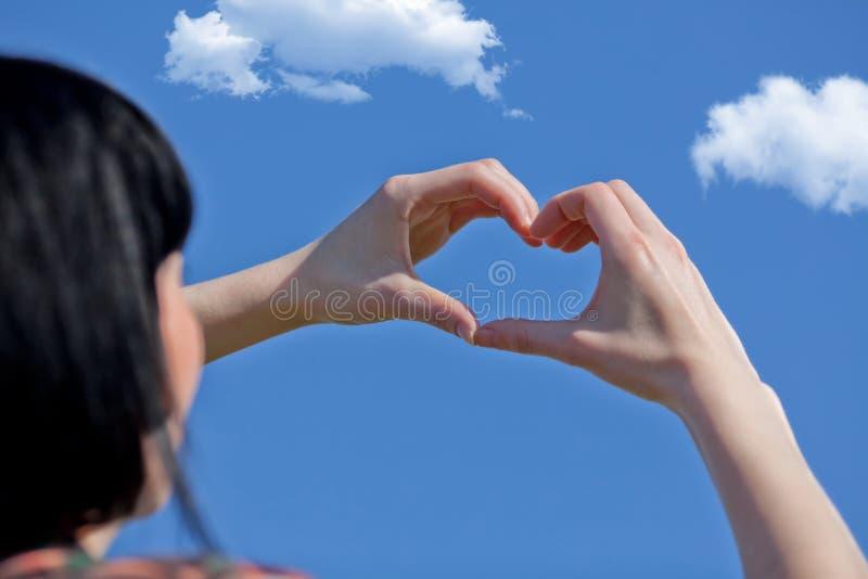 Mano de la muchacha en cielo azul del amor de la forma del corazón imágenes de archivo libres de regalías