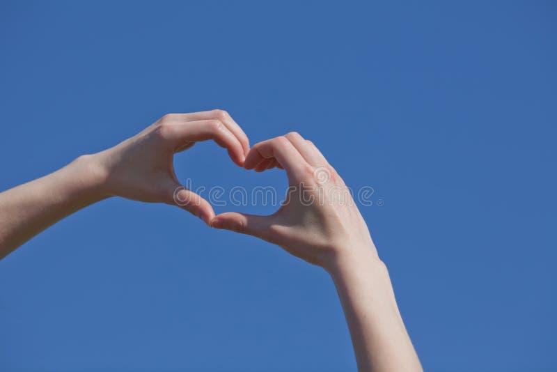 Mano de la muchacha en forma del corazón imagen de archivo