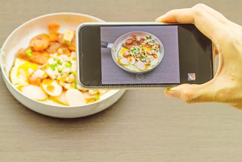 Mano de la muchacha que toma imágenes en un teléfono móvil en la cacerola de Indochina imagen de archivo libre de regalías