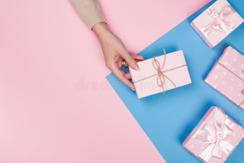 Mano de la mujer con la caja de regalo en fondo azul y rosado imagenes de archivo