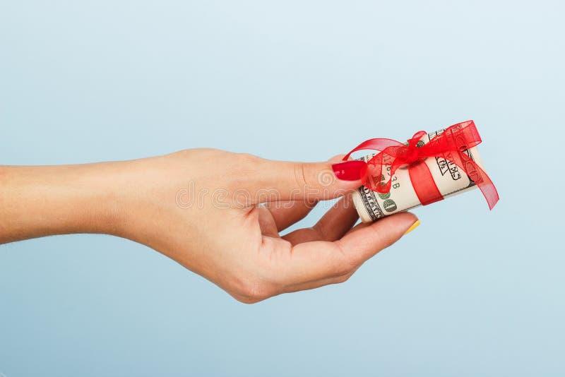 Mano de la mujer con el dinero en el fondo azul fotos de archivo libres de regalías