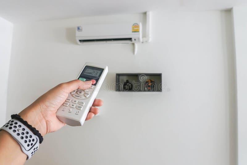 Mano de la mujer con el panel teledirigido del acondicionador de aire para el ajuste de temperatura imagenes de archivo