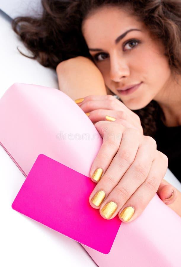 Mano de la mujer con la tarjeta de visita para el salón de belleza foto de archivo