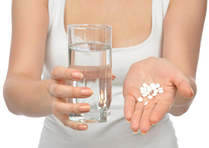Mano de la mujer con las tabletas de la medicina de las píldoras y el vidrio de agua foto de archivo libre de regalías