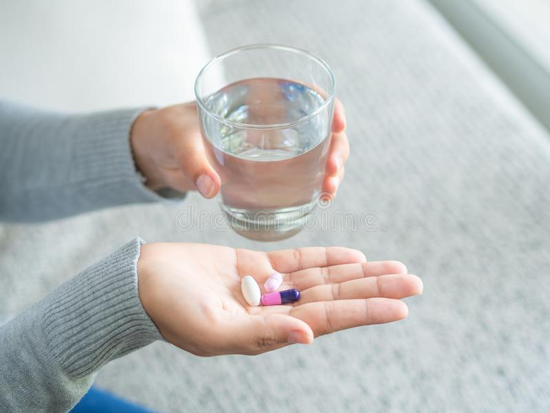 Mano de la mujer con las tabletas de la medicina de las píldoras y el vidrio de agua en ella fotos de archivo