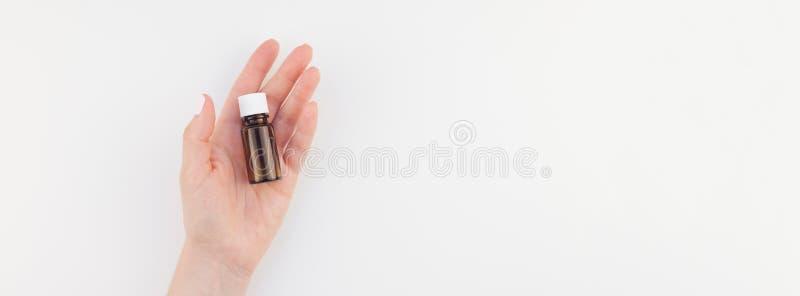 Mano de la mujer con la pequeña botella de cristal aislada imagen de archivo libre de regalías