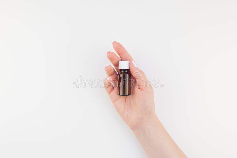 Mano de la mujer con la pequeña botella de cristal aislada fotos de archivo