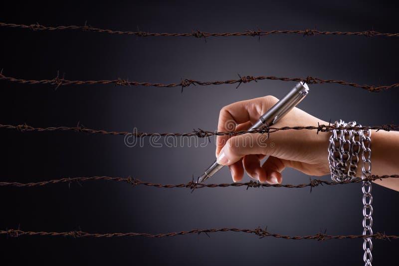 Mano de la mujer con la pluma atada con la cadena y el alambre desnudo agudo oxidado, representando la idea de la libertad de pre fotografía de archivo