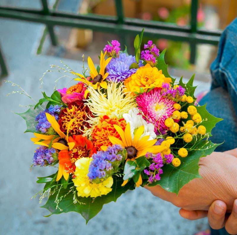 Mano de la mujer con un ramo de wildflowers imagen de archivo