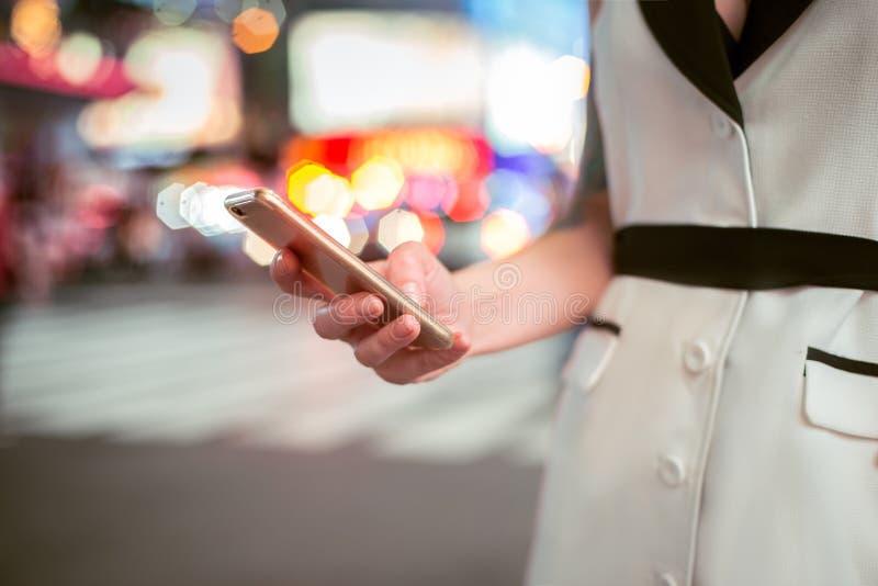 mano de la mujer de negocios que manda un SMS en el teléfono celular en la calle de New York City de la noche Empresaria que usa  foto de archivo libre de regalías