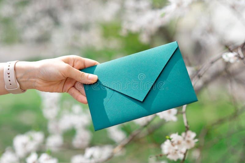 Mano de la mujer del primer que sostiene una tarjeta de la invitación, vista delantera imagen de archivo libre de regalías