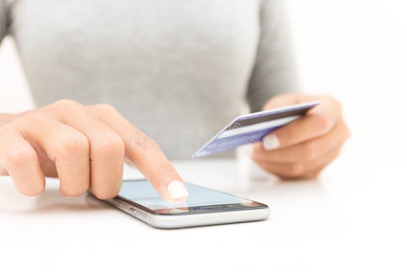 mano de la mujer del primer usando el teléfono y compras de la tarjeta de crédito fotos de archivo libres de regalías