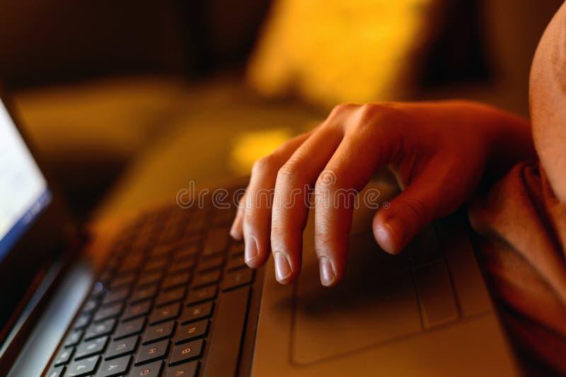 Mano de la mujer en concepto de Ministerio del Interior del funcionamiento del teclado del ordenador port?til en casa foto de archivo