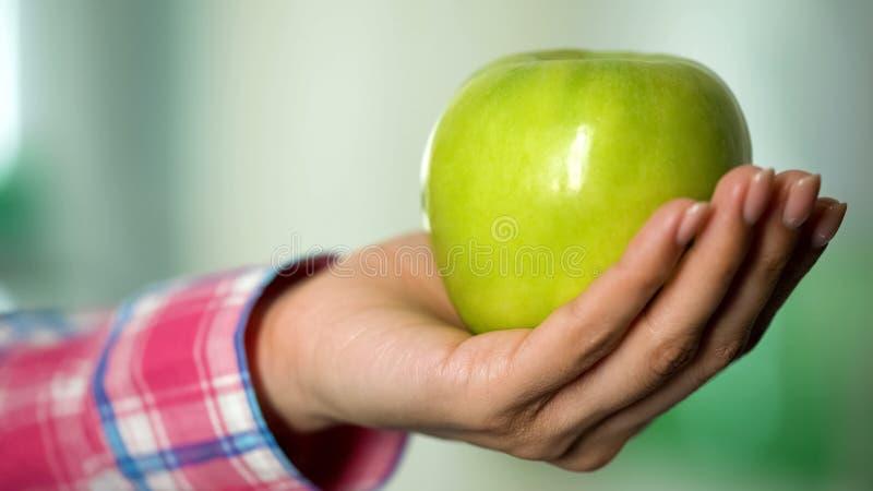 Mano de la mujer joven que muestra el primer verde de la manzana, el alimento biológico para la salud y la belleza fotografía de archivo libre de regalías