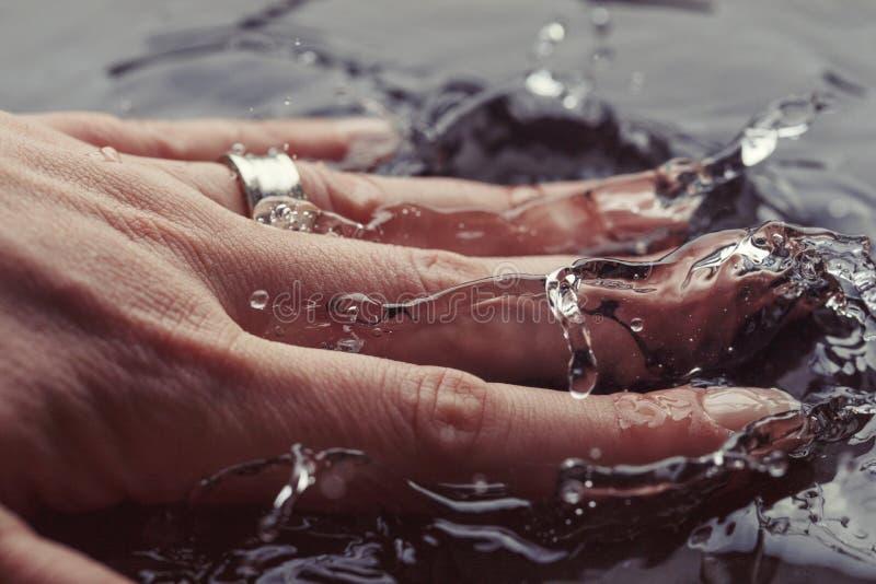 Mano de la mujer joven que salpica en el agua potable, detalle extremo del primer Fondo macro del concepto de la fotografía de al imágenes de archivo libres de regalías