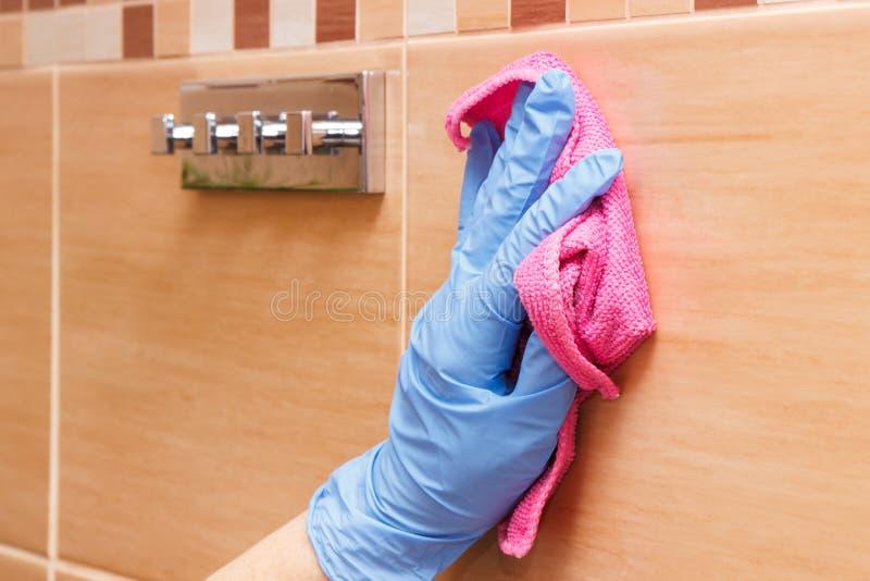 Mano de la mujer mayor que lava y que limpia las tejas del cuarto de baño usando el paño rosado de la microfibra, concepto de los foto de archivo