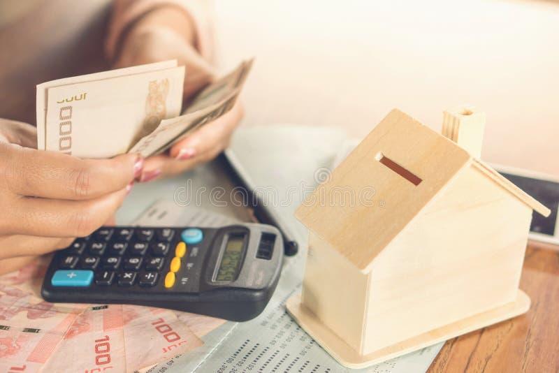 Mano de la mujer de negocios que cuenta el billete del dinero con el libro de cuentas de ahorro, el modelo de la casa y la calcul fotografía de archivo