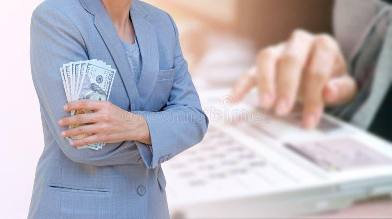 Mano de la mujer de negocios que lleva a cabo el pasaporte y el dólar americano Currenc imagenes de archivo