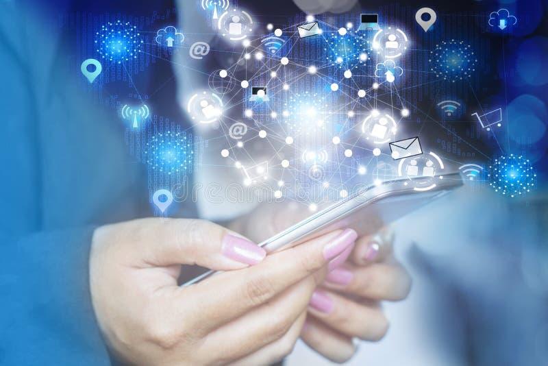 Mano de la mujer de negocios que sostiene el teléfono elegante con Internet del icono de cosas imagen de archivo