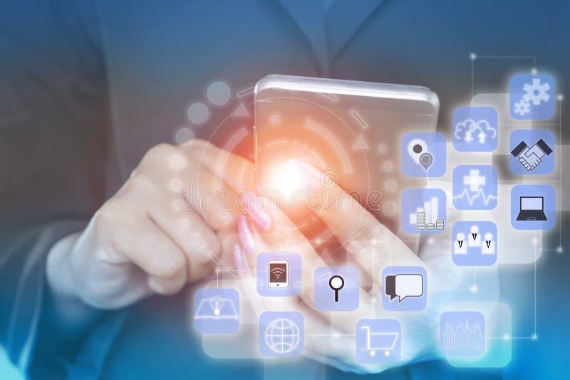 Mano de la mujer de negocios que sostiene el teléfono elegante con los iconos de la tecnología foto de archivo