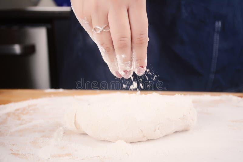 Mano de la mujer que añade la harina a la pasta foto de archivo