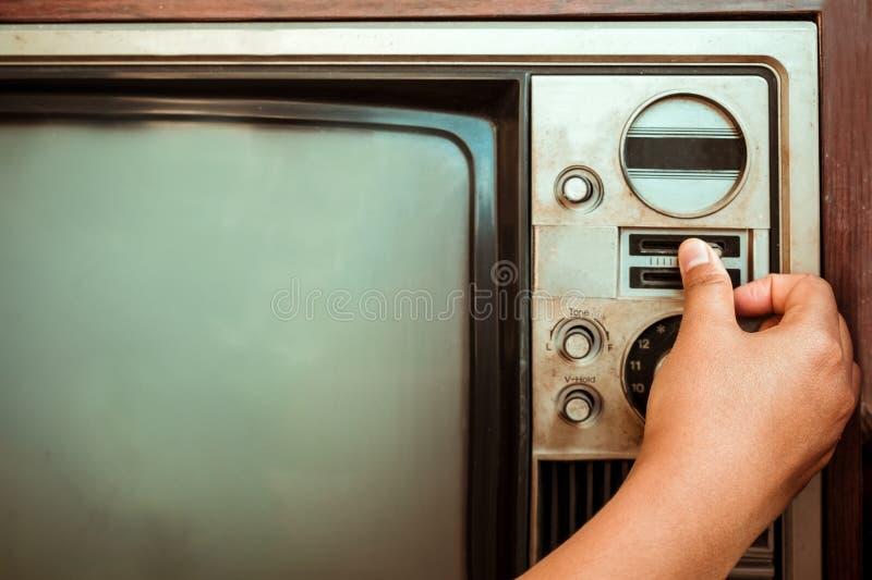 Mano de la mujer que ajusta la televisión del vintage con el botón del control fotos de archivo