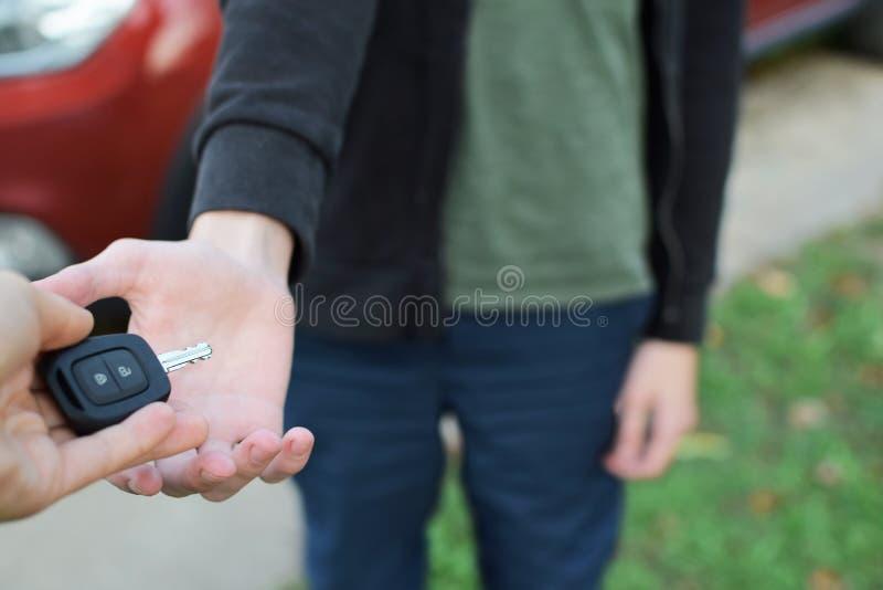 Mano de la mujer que da llave del coche foto de archivo libre de regalías