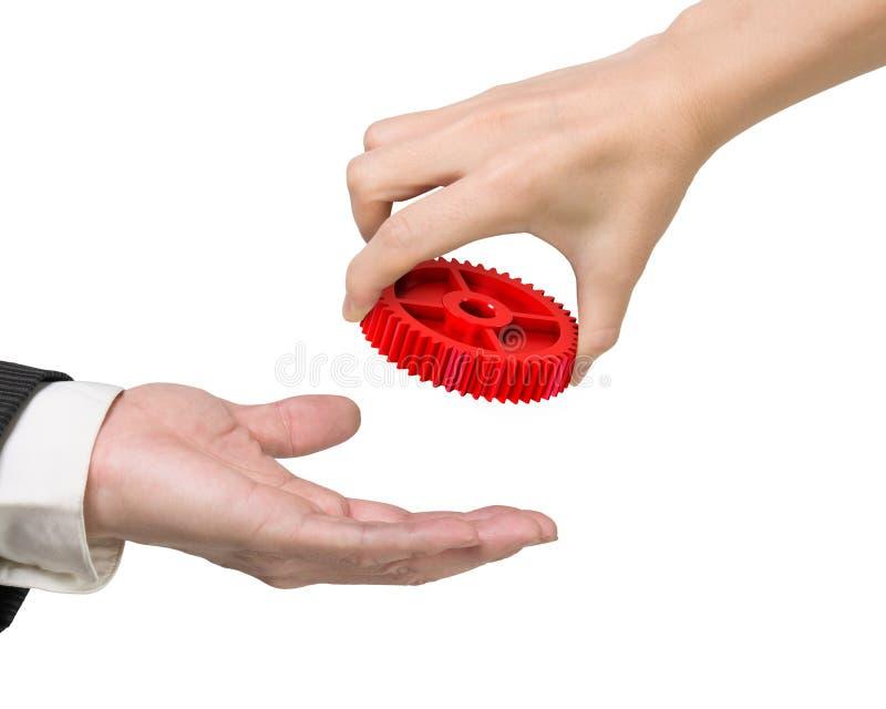 Mano de la mujer que da un engranaje rojo a la mano del hombre fotografía de archivo